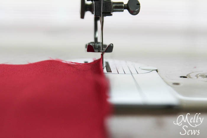With a regular foot, line fabric fold up to needle
