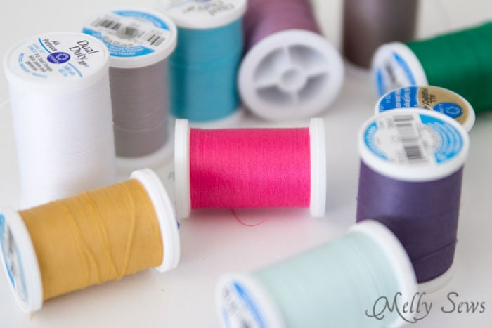 An assortment of different colored spools of all purpose sewing thread