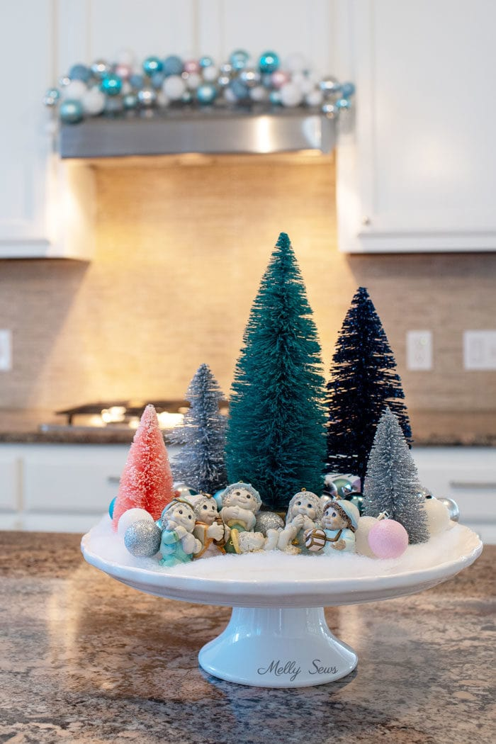 Bottle brush tree tablescape - kitchen island Christmas decor with ornament swag over stove in the background