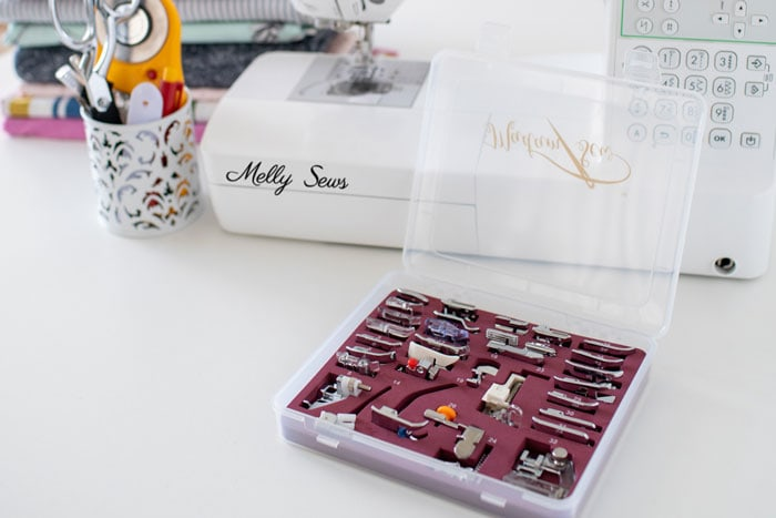 Box of presser feet for sewing in front of a sewing machine, sewing notions and a stack of fabric