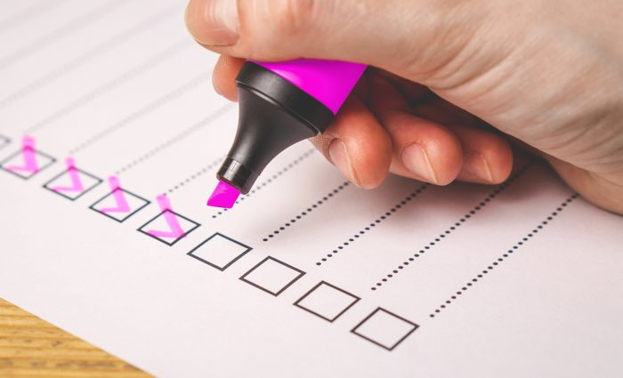 Person using a checklist to mark completed tasks