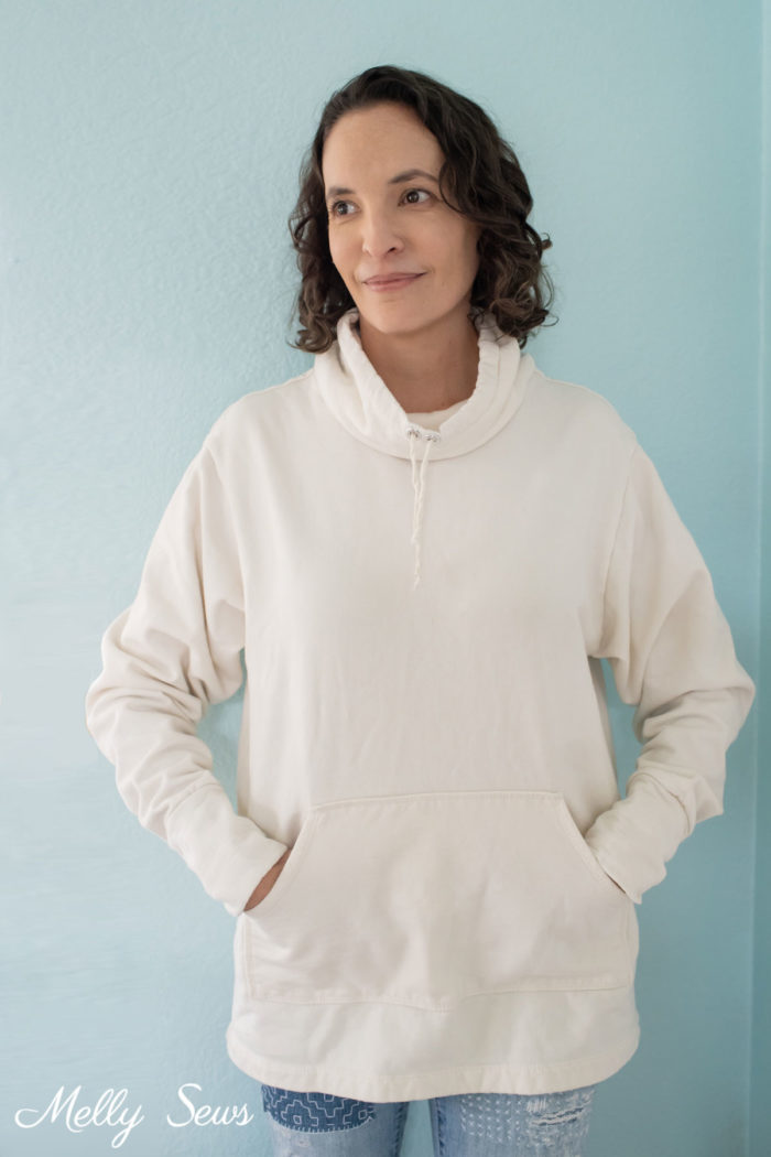 Brown haired woman wearing an ivory sweatshirt with a drawstring cowl neck
