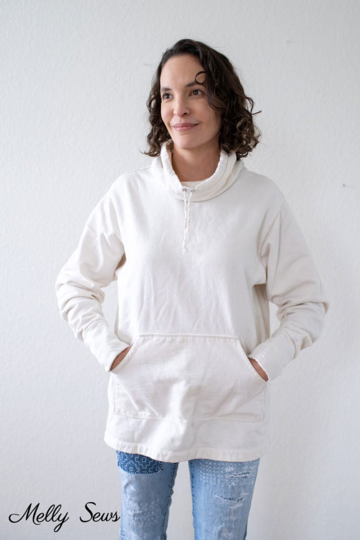 Woman wearing mended jeans and an ivory sweatshirt with a cowl neckline