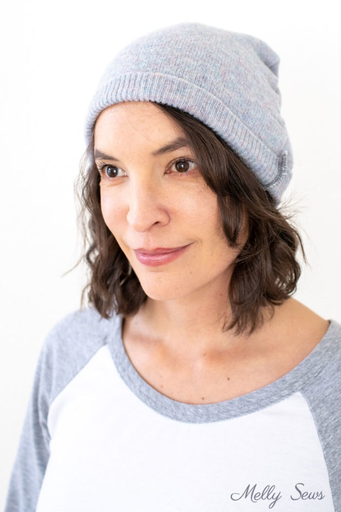 Woman wearing a gray beanie made from a thrifted sweater