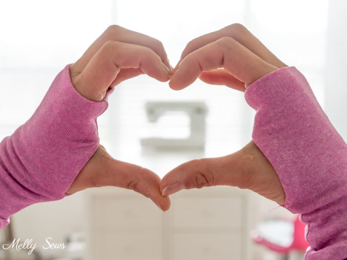 Hands wearing pink thumbhole cuffs forming a heart around a sewing machine