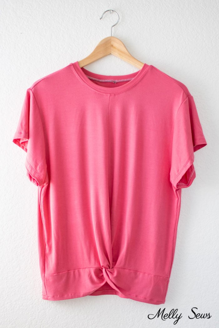 Pink shirt with a twist bottom hem hanging on a hanger