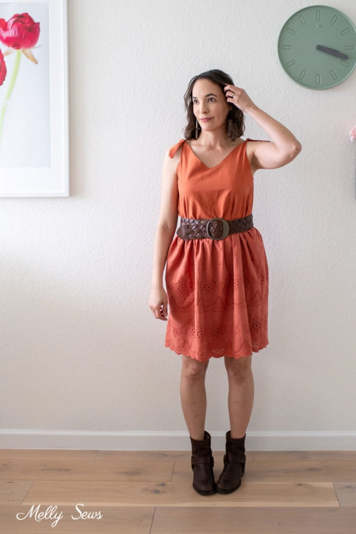 Woman wearing a rust colored dress upcycled from a thrifted dress