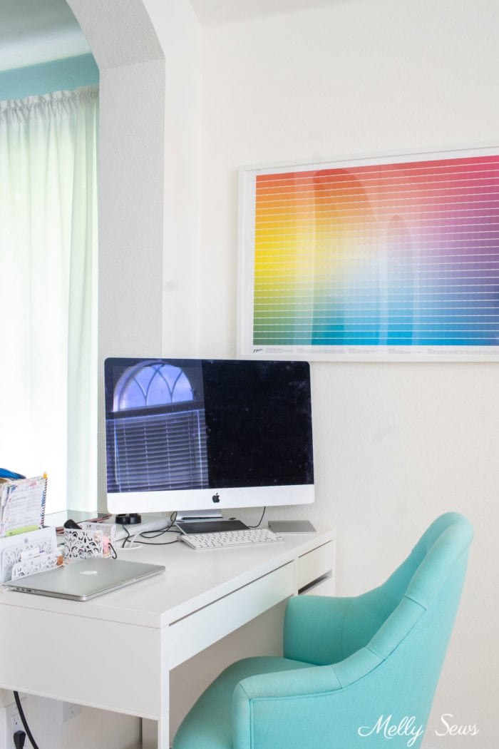 Creative home office space with a white desk, teal chair and color chart poster on the wall