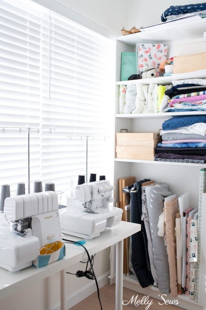 Serger, cover stitch machines and a bookshelf full of fabric