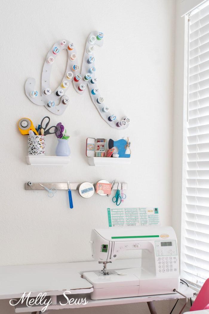 Sewing machine on vintage table below magnetic storage, floating shelves and custom thread spool holder