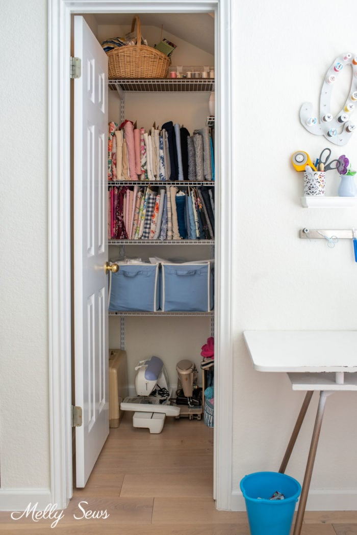 Closet door opening to show shelves of fabric and sewing machines in a sewing room