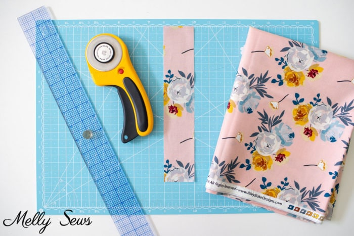 Quilting ruler, rotary cutter, strip of fabric cut straight and folded fabric laying on a cutting mat