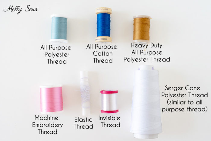 Different kinds of sewing thread - light blue all purpose polyester thread, bright blue all purpose cotton thread, gold heavy duty all purpose polyester thread, pink rayon machine embroidery thread, elastic thread, invisible thread, and white serger cone polyester thread