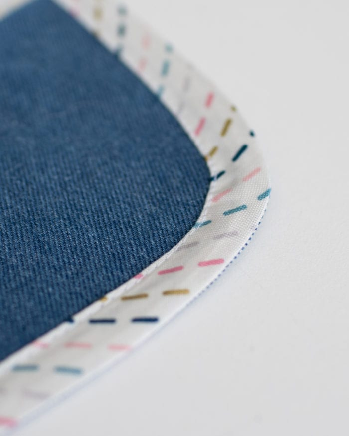 A curved corner of fabric with bias tape sewn around the curve
