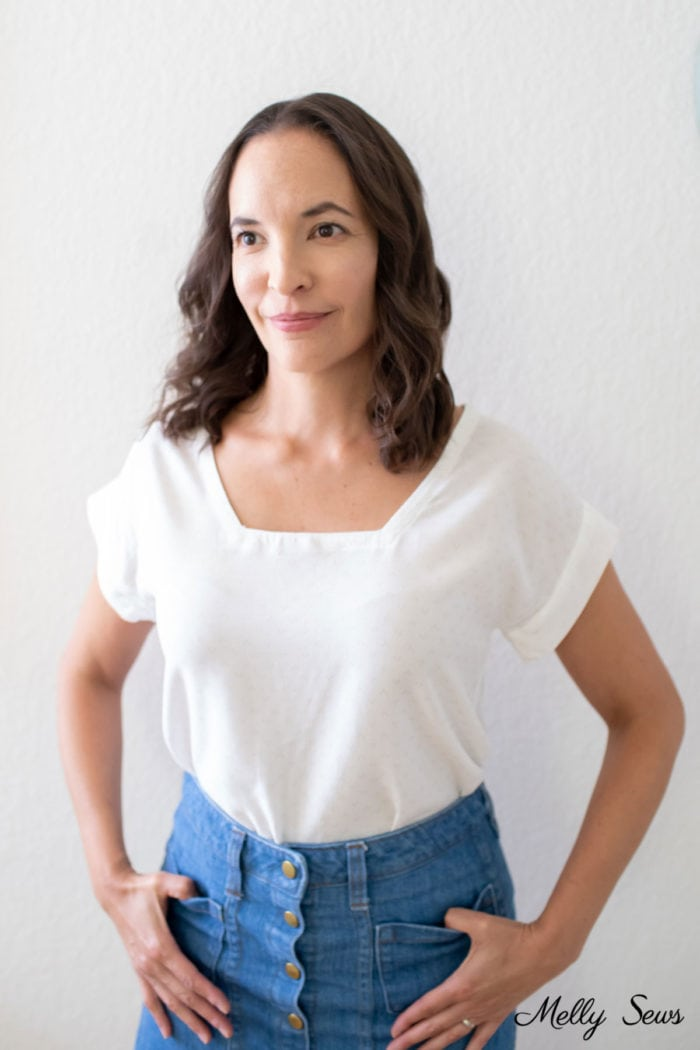 Woman wearing a handmade white blouse with a square neckline and blue denim skirt - learn to change necklines on tops