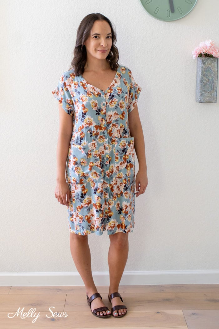 Woman wearing a handmade button front dress in floral fabric with pockets