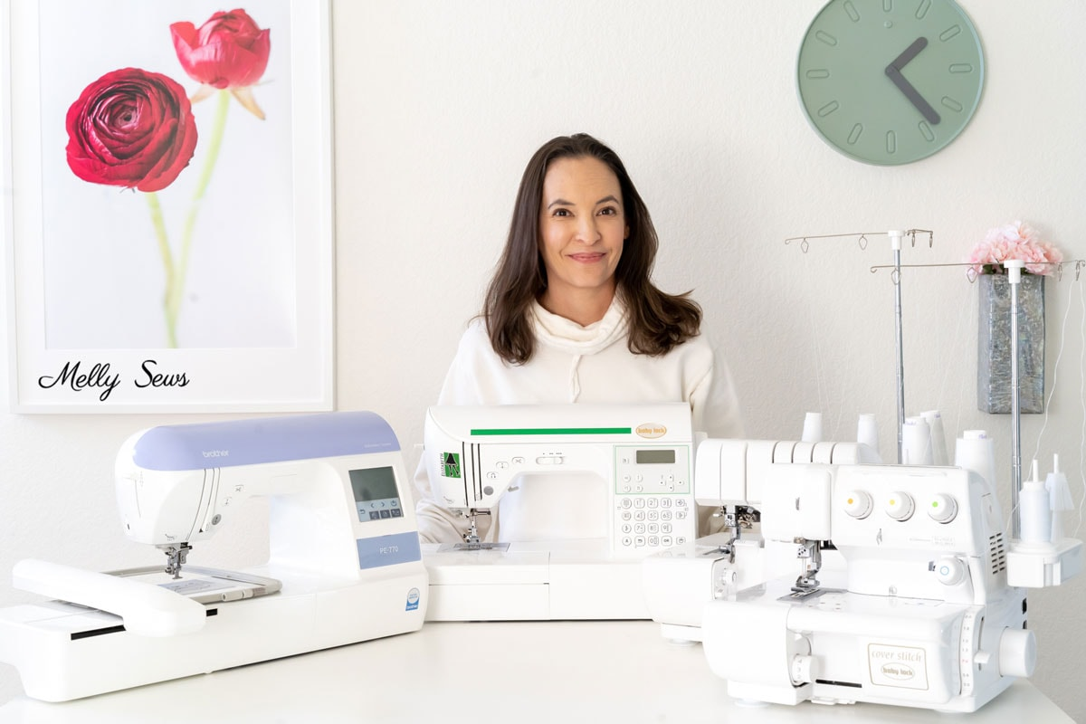 Woman with different kinds of sewing machines - embroidery machine, sewing machine, serger and cover stitch.
