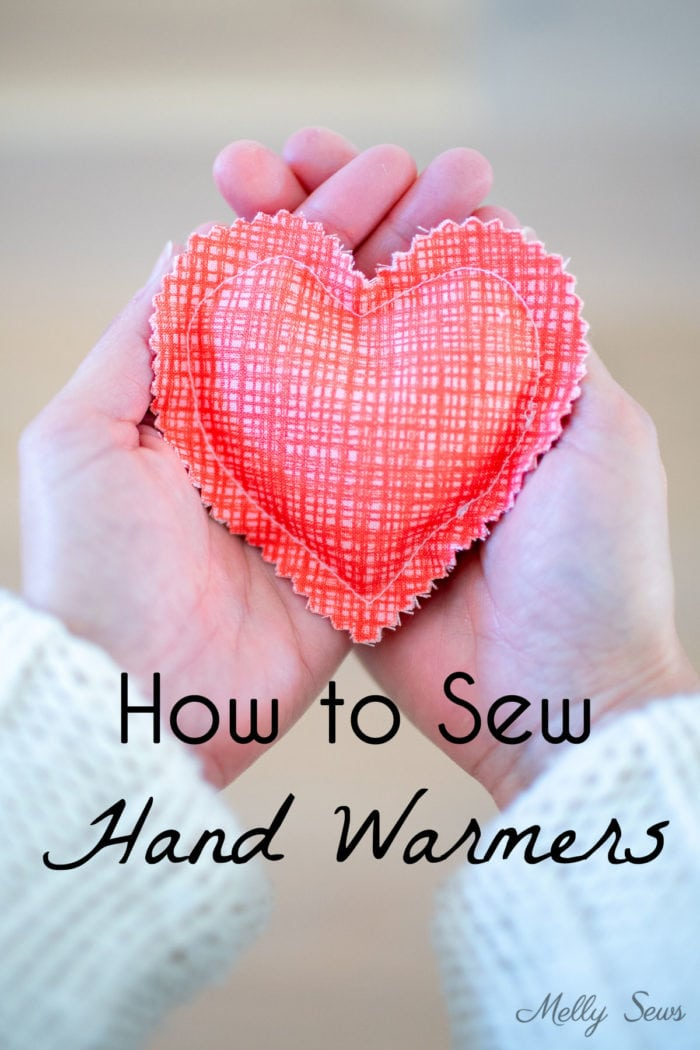 Hands holding a heart shaped DIY hand warmer sewn in coral colored fabric