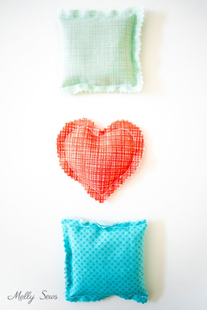 Three hand warmers to sew in Riley Blake fabrics - a mint green square, coral colored heart shaped one and a turquoise square one