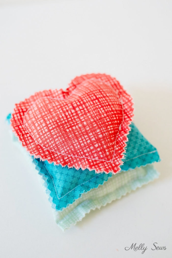Stack of rice filled hand warmers, a mint green square, a turquoise square one and a coral colored heart shaped one on top