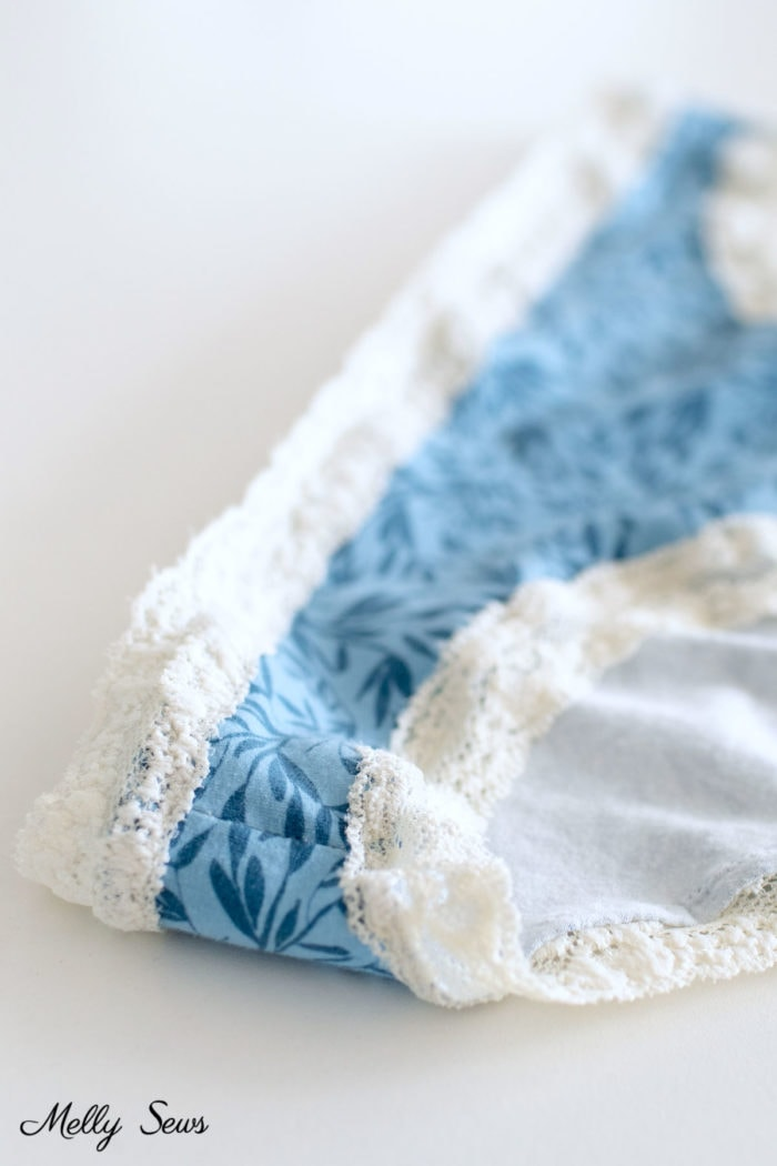 Close up of ivory elastic lace trim sewn to a pair of blue floral panties