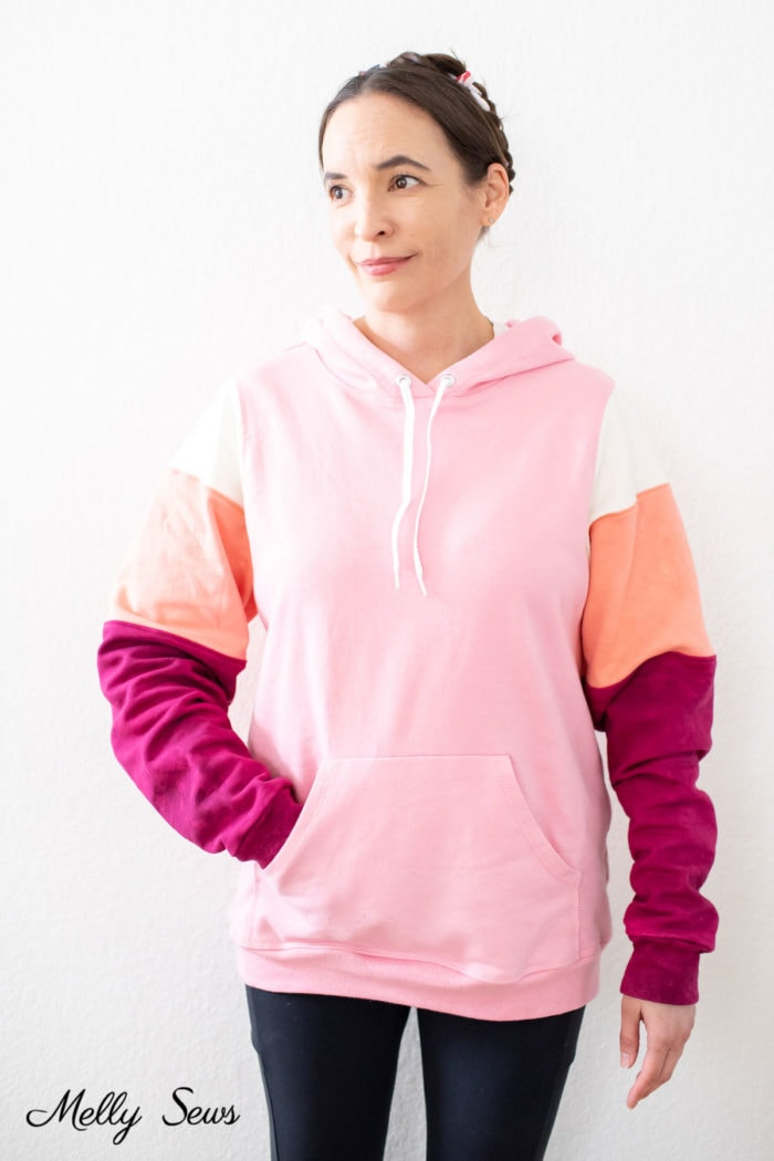 Woman wearing a hoodie in pink, ivory, coral and maroon fabric