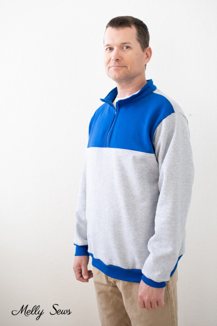 Man wearing a blue and gray half zip pullover sweatshirt