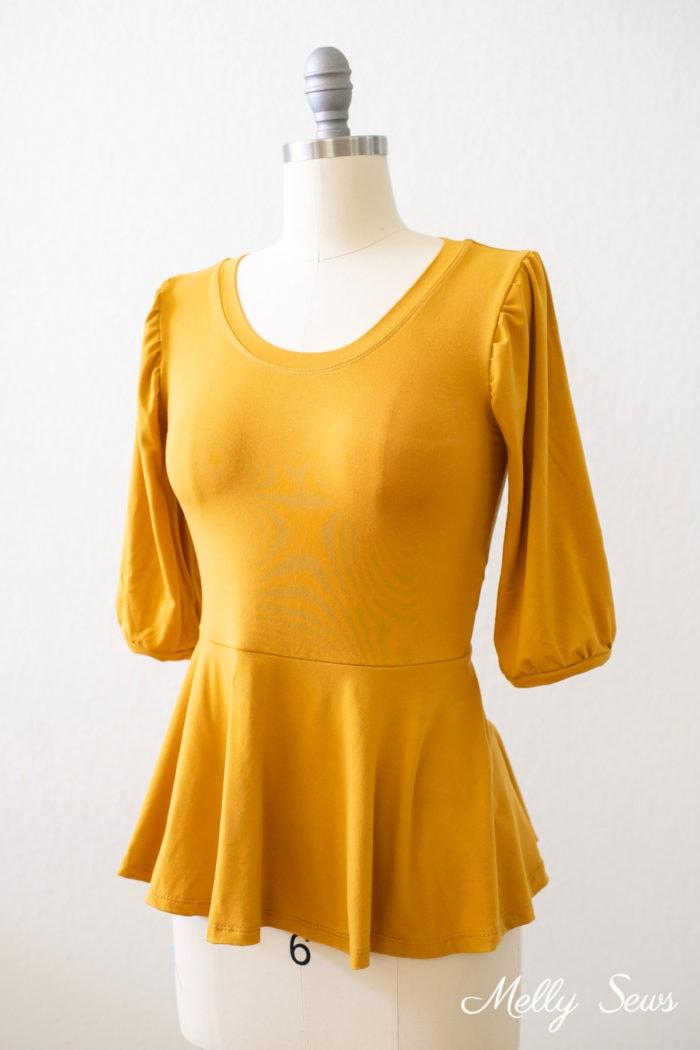 Top peplum dorado con mangas abullonadas en forma de vestido