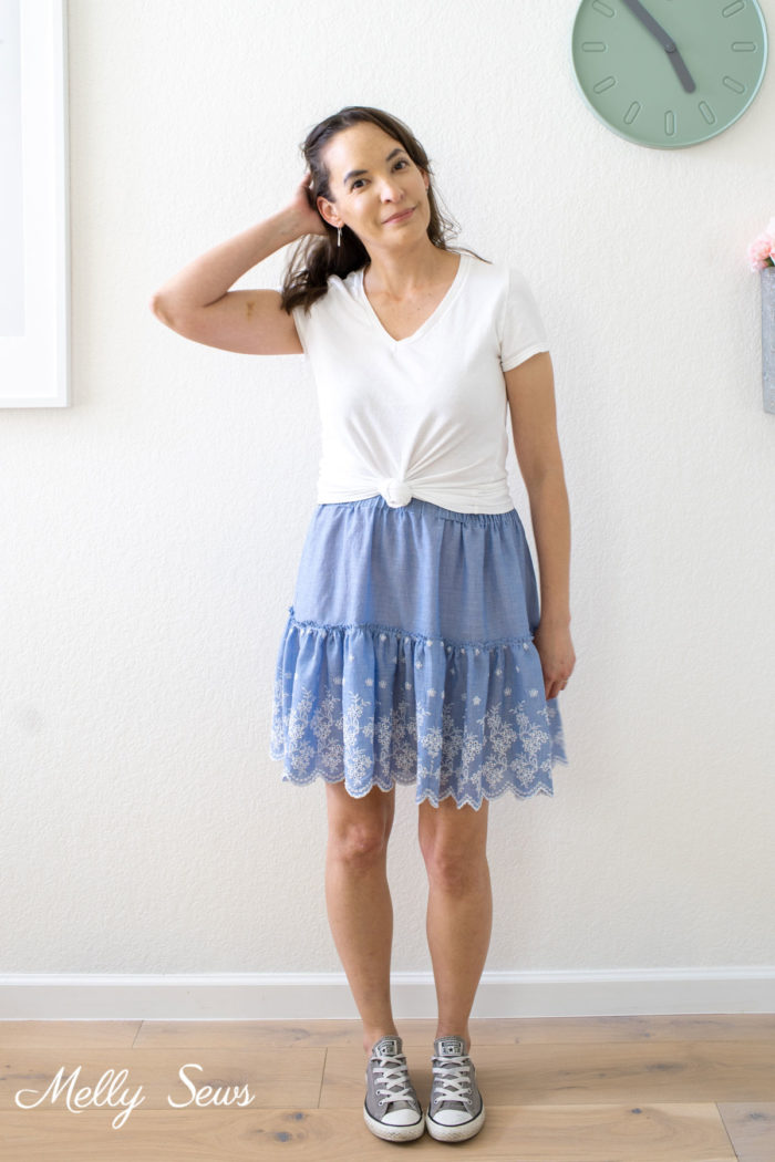 Woman in a white t-shirt and DIY blue ruffled skirt and sneakers