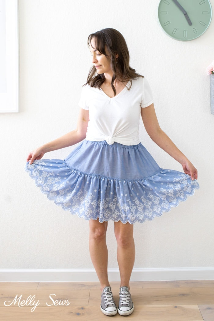 A brown haired woman in a white t-shirt and a blue gathered skirt she sewed