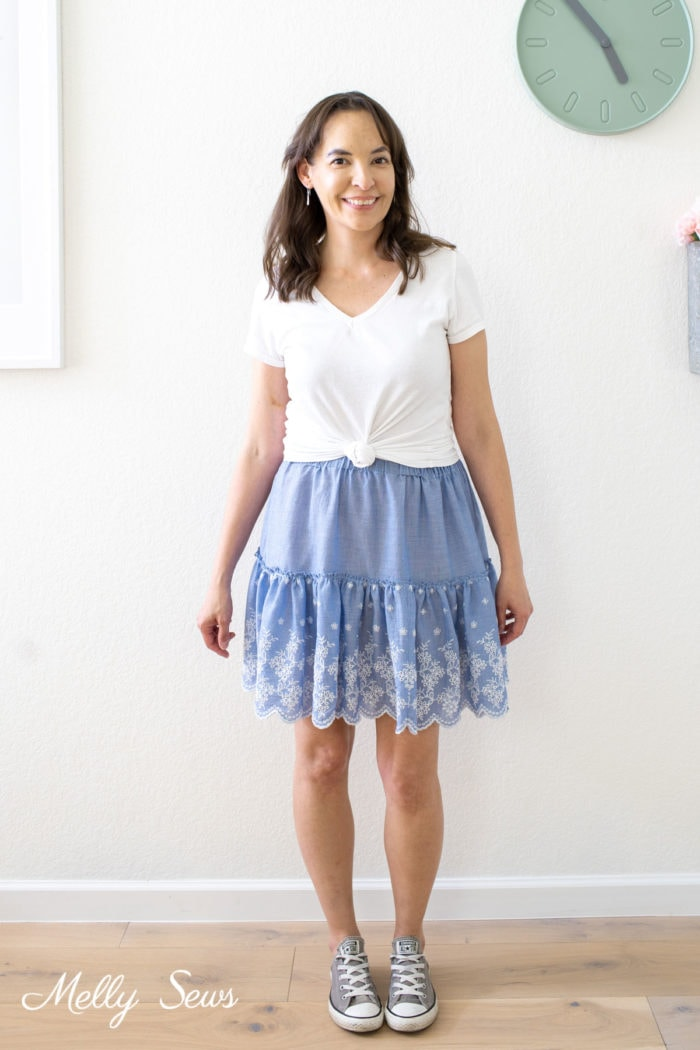 Woman in a summer outfit of a white t-shirt and blue tiered skirt