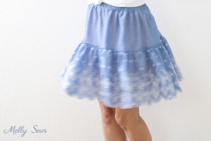 A blue ruffled skirt blurs as the person wearing it turns