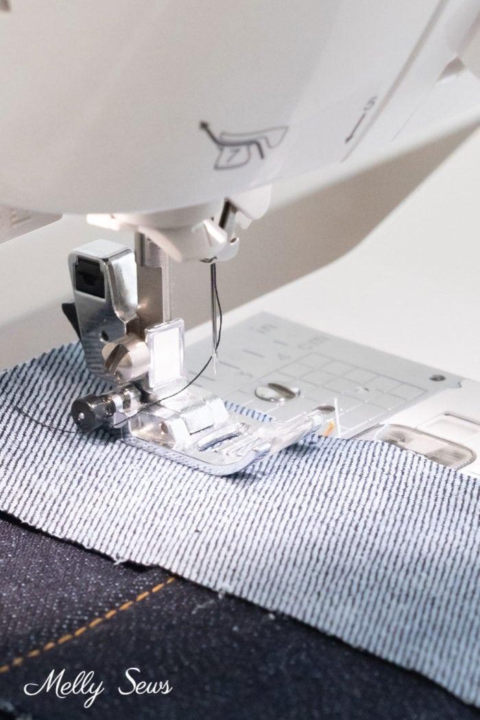 Close up of a sewing machine presser foot sewing denim