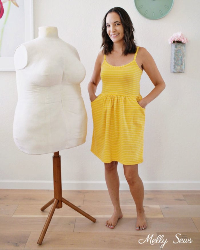 Women in a yellow dress standing next to a plus size mannequin she sewed